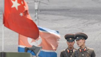 "North Korean soldiers chat as they stand guard behind national flags of China (front) and North Korea on a boat anchored along the banks of Yalu River, near the North Korean town of Sinuiju, opposite the Chinese border city of Dandong, June 10, 2013. North and South Korea opened their first official talks in two years on Sunday at a border village ""without argument"", the South said, building on an easing in tensions from nearly daily threats two months ago of impending nuclear war.    REUTERS/Jacky Chen (NORTH KOREA - Tags: MILITARY POLITICS)"