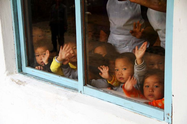 Children at Samchon Nursery School wave from a window. Children here receive soy, oil and cereal milk blend.  The food is don