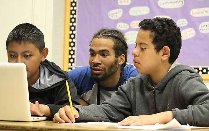 Aim High teacher Malik Beale with 8th grade students who are creating a project on immigration.