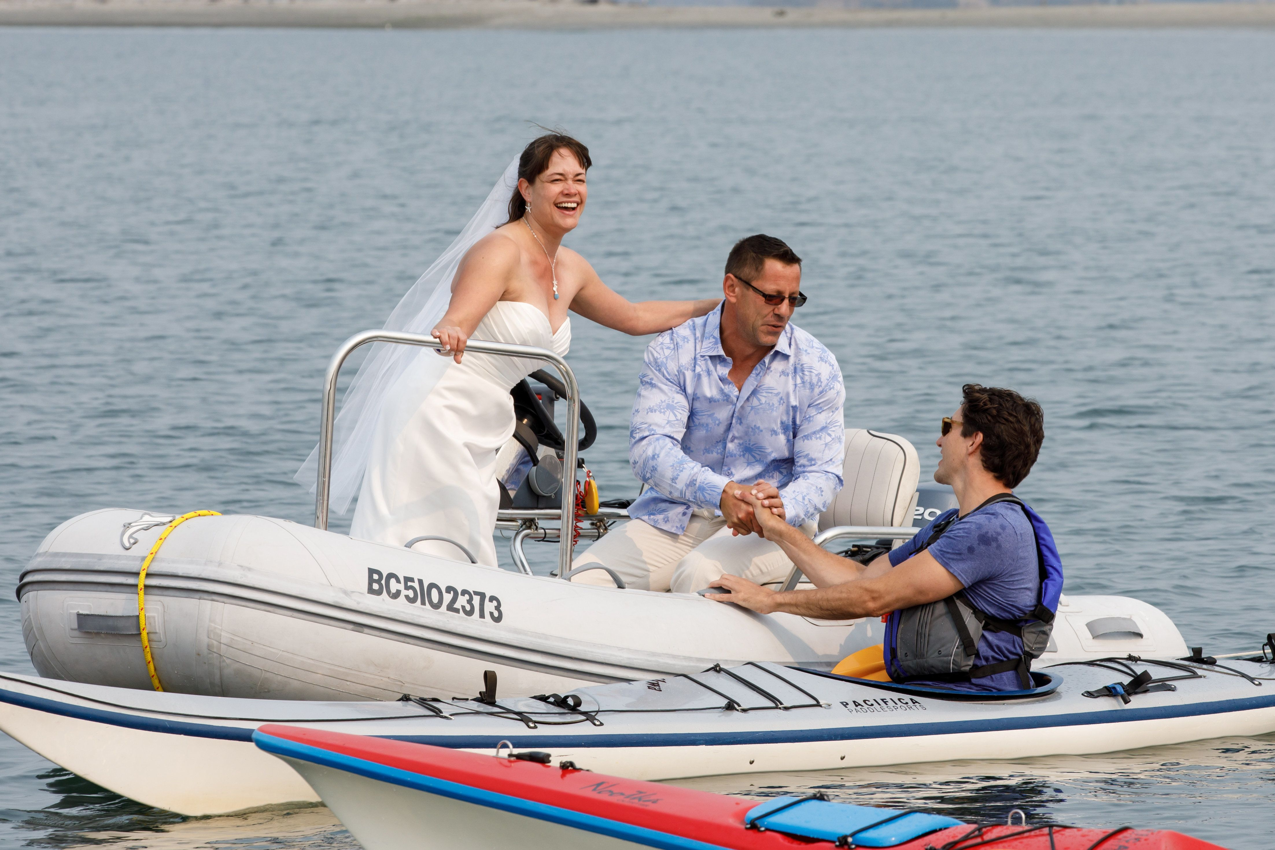 Newlyweds Michelle and Heiner Gruetzner, who were holding their wedding reception nearby, approach Canada's Prime Minister Justin Trudeau while he was kayaking off Sidney, British Columbia, Canada August 5, 2017.  Adam Scotti/Prime Minister's Office/Handout via REUTERS.  ATTENTION EDITORS - THIS IMAGE WAS PROVIDED BY A THIRD PARTY