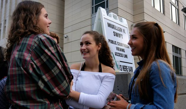 Grace Jarecke, 16, left, Lucy Peterson, 17, and Dani Kuta, 17, right, all from Denver, wait in line to...