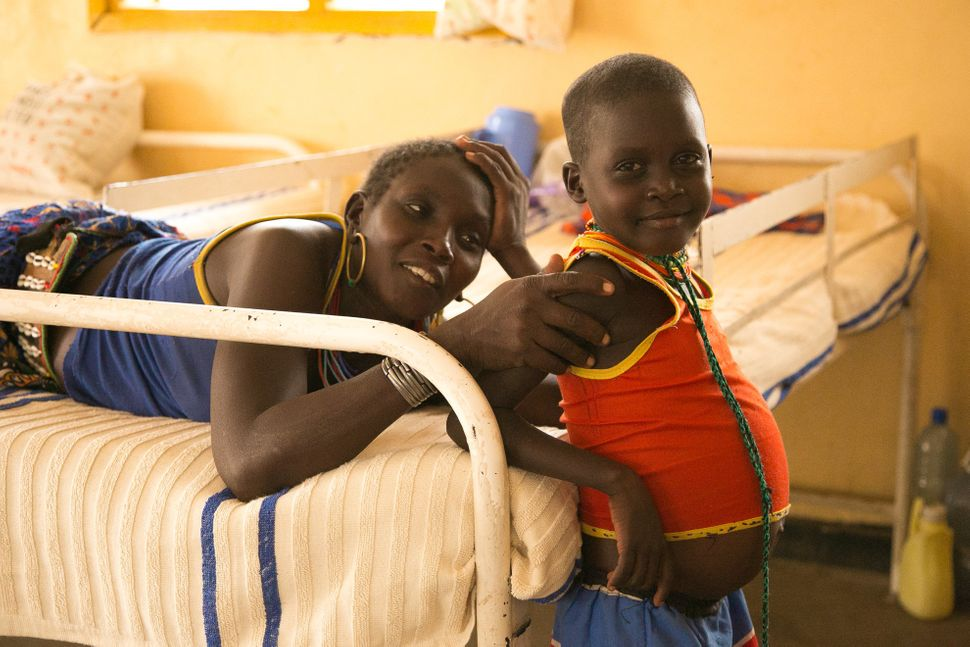 A mother sits with her child, who is being treated for kala azar in the specialty ward atKacheliba Hospital in western