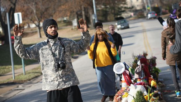 FERGUSON, MO - NOVEMBER 29:  David Whitt (L) and others march around the Michael Brown memorial on November 29, 2014 in Ferguson, Missouri. The Ferguson area has been struggling to return to normal since the August 9 shooting of Brown, an 18-year-old black man, who was killed by Darren Wilson, a white Ferguson police officer. When the grand jury announced on November 24, that Wilson would not face charges in the shooting rioting and looting broke out throughout the area leaving several businesses burned to the ground.  (Photo by Scott Olson/Getty Images)