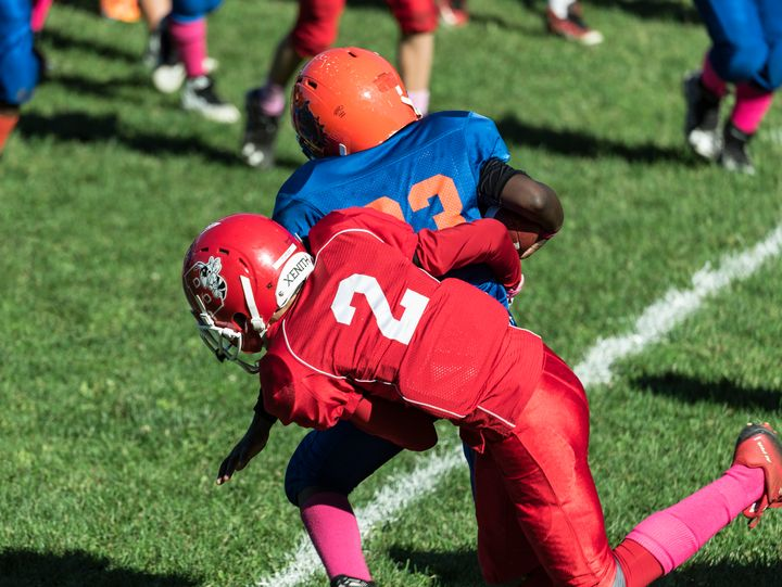 Boys make a tackle during a youth football game. Dr. Bennet Omalu, the man credited with discovering CTE, believes child