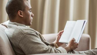 Side view of African American man relaxing at home and reading a book.