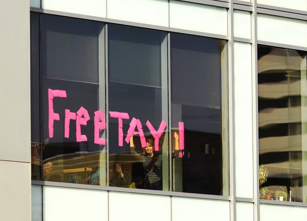People wrote 'Free Tay!' with sticky notes in an office window across the street from the Alfred A. Arraj...