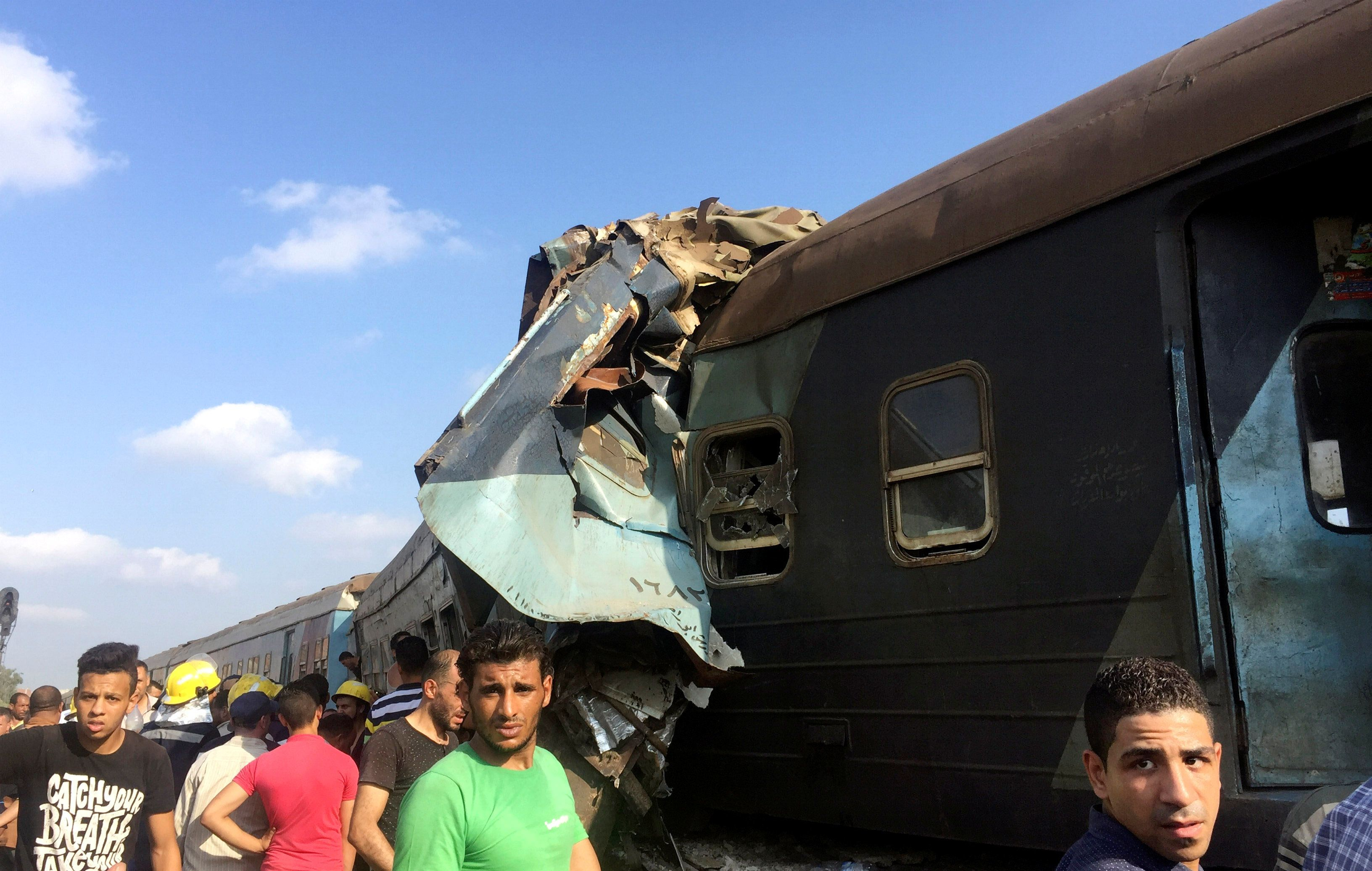 Egyptians look at the crash of two trains that collided near the Khorshid station in Egypt's coastal city of Alexandria, Egyp