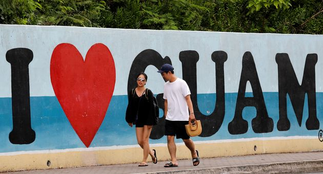Tourists stroll along a road on the island of Guam on August 10,