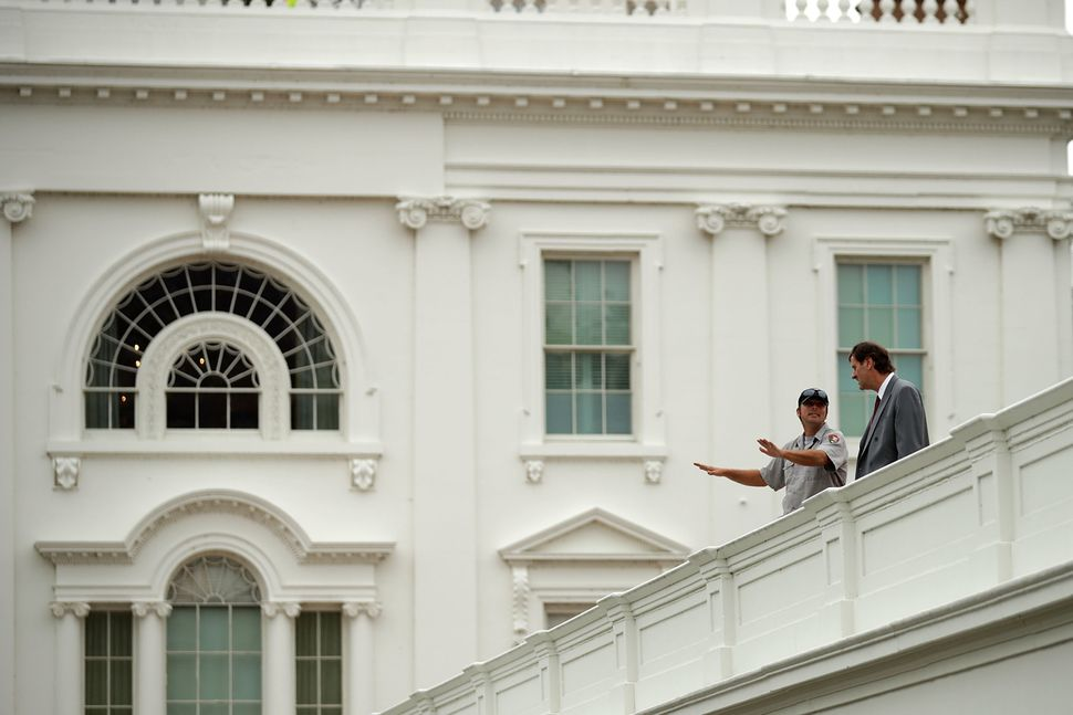 National Park Service workers stand on the roof of the West Wing.