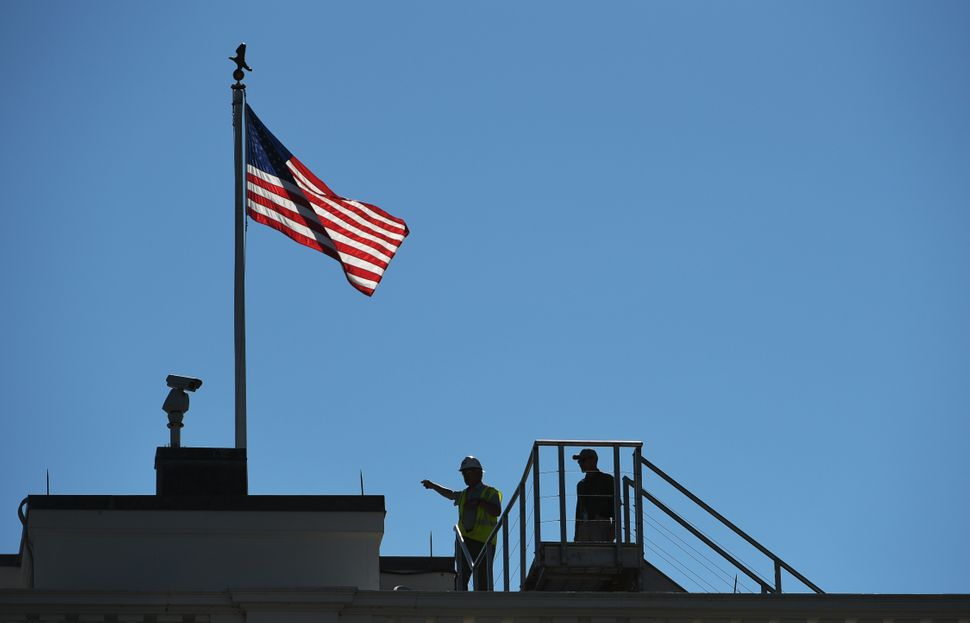 A worker is seen on the roof of the White House.