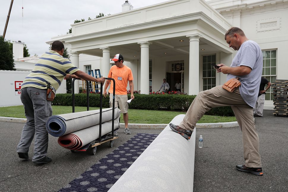 Workers measure and cut new carpeting in the driveway outside the West Wing.