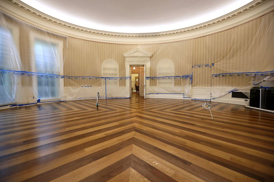 The Oval Office sits empty and the walls are covered with plastic sheeting during renovation work.