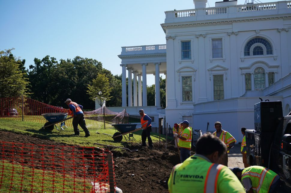 Workers are seen on the lawn outside of the Brady Briefing Room.