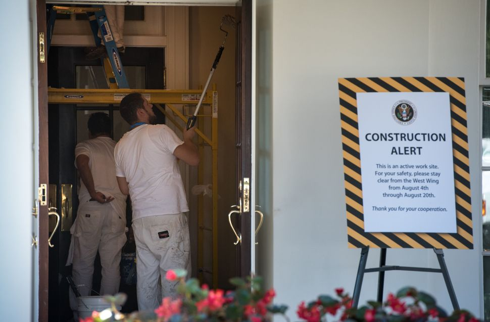 Workers are seen painting inside a West Wing entrance.