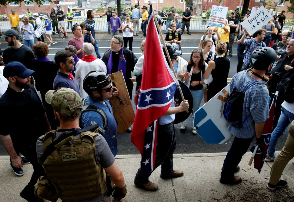 A white supremacist carries the Confederate flag as he walks past counter-demonstrators.