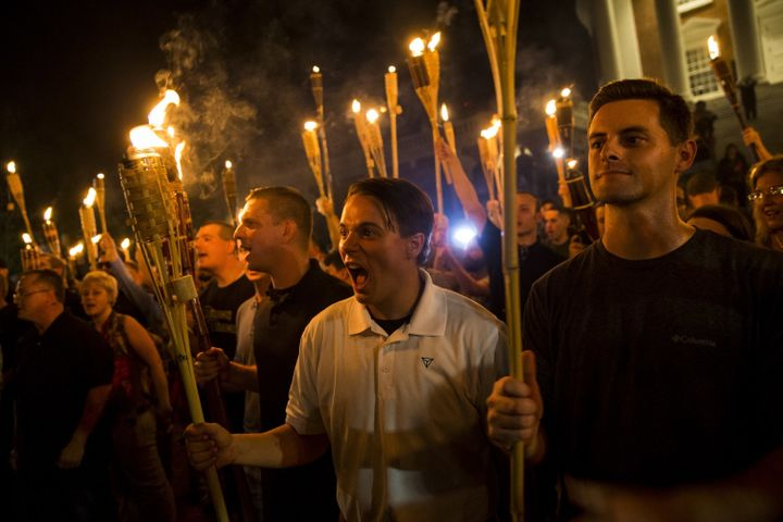 A white woman (far left) protests with a torch at the University of Virginia with neo-Nazis.