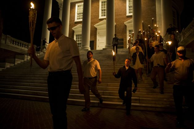 A white woman (right) walks down the steps witha group of neo-Nazis at the University of Virginiaon...