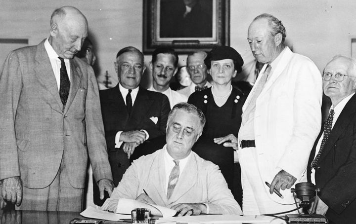 President Franklin D. Roosevelt signs Social Security into law.