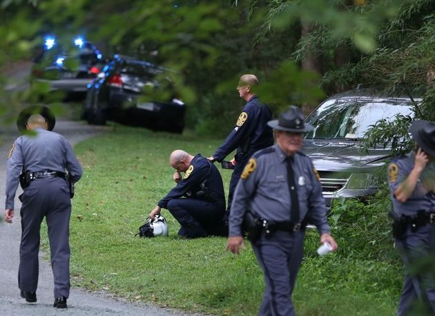 A Virginia law enforcement officer cries near the site of a state police helicopter crash, which killed...