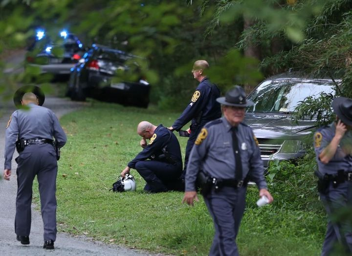 A Virginia law enforcement officer cries near the site of a state police helicopter crash, which killed two state troopers.