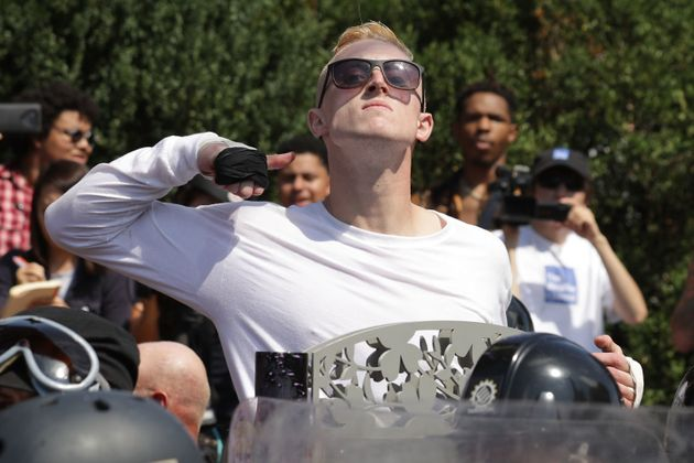 A man makes a slashing motion across his throat toward counter-protesters as he marches with white nationalists,...