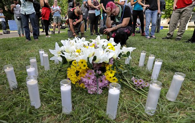 People pay their respects at a vigil where 20 candles were burned for the 19 people injured and one killed...