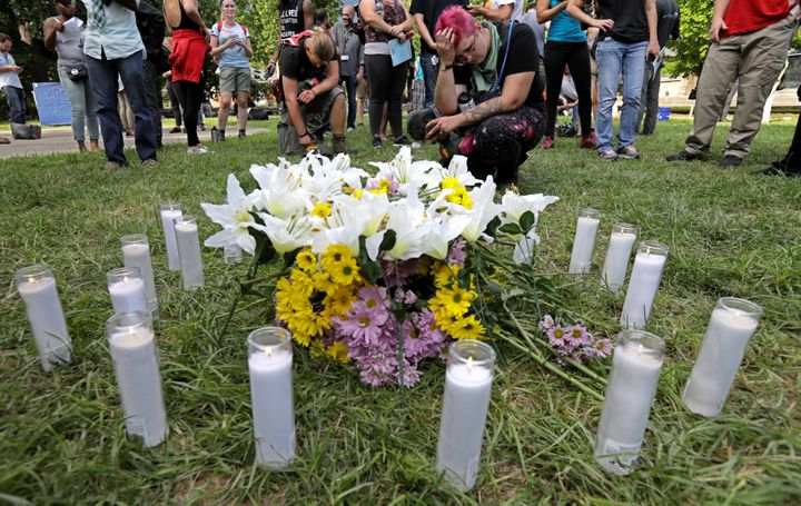 People pay their respects at a vigil where 20 candles were burned for the 19 people injured and one killed when a car plowed into a crowd of counter-protesters at the