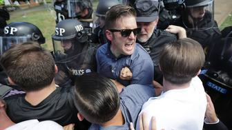 CHARLOTTESVILLE, VA - AUGUST 12:  White nationalist Richard Spencer (C) and his supporters clash with Virginia State Police in Lee Park after the 'Unite the Right' rally was declared an unlawful gathering August 12, 2017 in Charlottesville, Virginia. Hundreds of white nationalists, neo-Nazis and members of the 'alt-right' clashed with anti-fascist protesters and police as they attempted to hold a rally in Lee Park, where a statue of Confederate General Robert E. Lee is slated to be removed. (Photo by Chip Somodevilla/Getty Images)