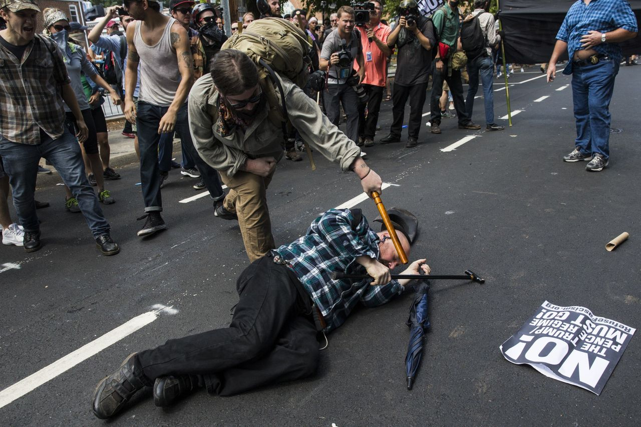 """A counter-protester strikes a white nationalist with a baton during clashes at Emancipation Park where the """"alt-right"""" was protesting the removal of the Robert E. Lee monument in Charlottesville, Virginia."""