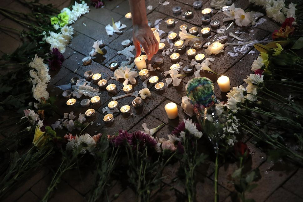 A man tends a makeshift candlelight vigil for those who died and were injured when a car plowed into a crowd of anti-fascist