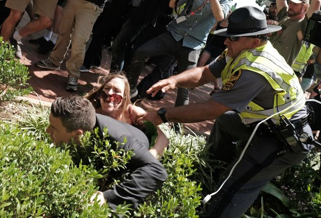 Unite The Right rally organiser Jason Kessler is helped by police after being tackled by a woman after...