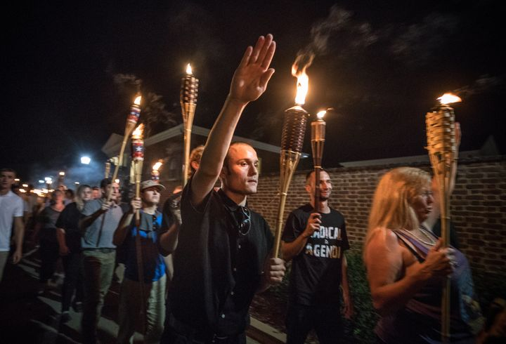 White supremacists and white nationalists carry lit Tiki torches while marching through the University of Virginia campus on