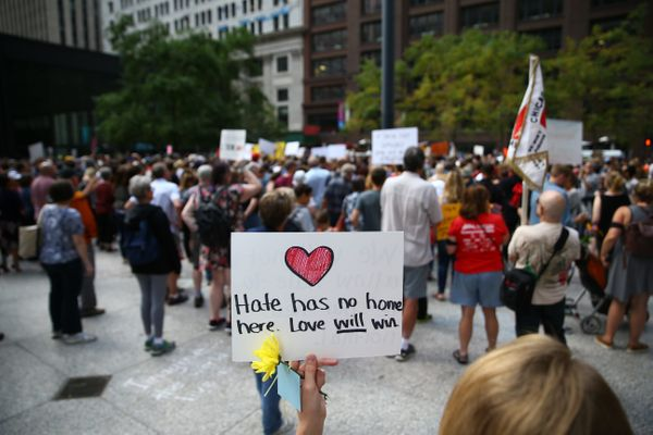 "A demonstrator holds a banner reading ""Hate Has No Home Here. Love Will Win"" during an Aug. 13 protest at Federal Plaza Squar"