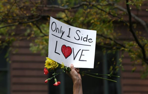 "A demonstrator holds a banner reading ""Only 1 Side Love"" during a protest at Federal Plaza Square in Chicago on Aug. 13."