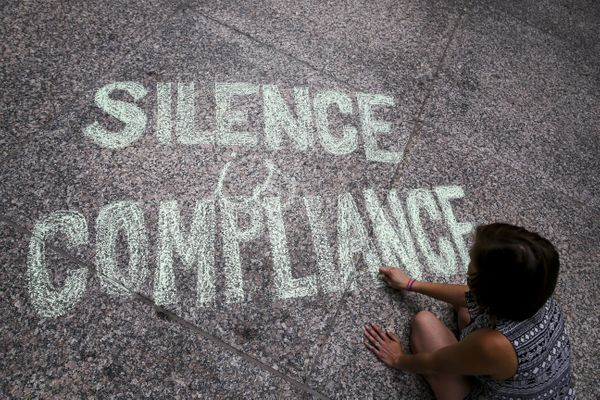 "A woman writes ""Silence is Compliance"" with a chalk on the ground at Federal Plaza Square in Chicago during an Aug. 13 p"
