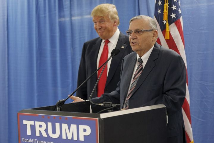 Then-presidential candidate Donald Trump listens to the endorsement of Maricopa County Sheriff Joe Arpaio before a campa
