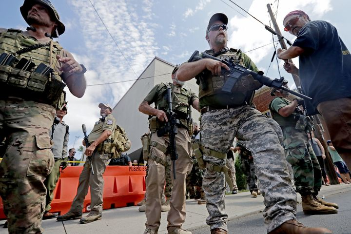 "Armed militia members look on after Saturday's ""United the Right"" rally in Charlottesville was declared an unlawful"