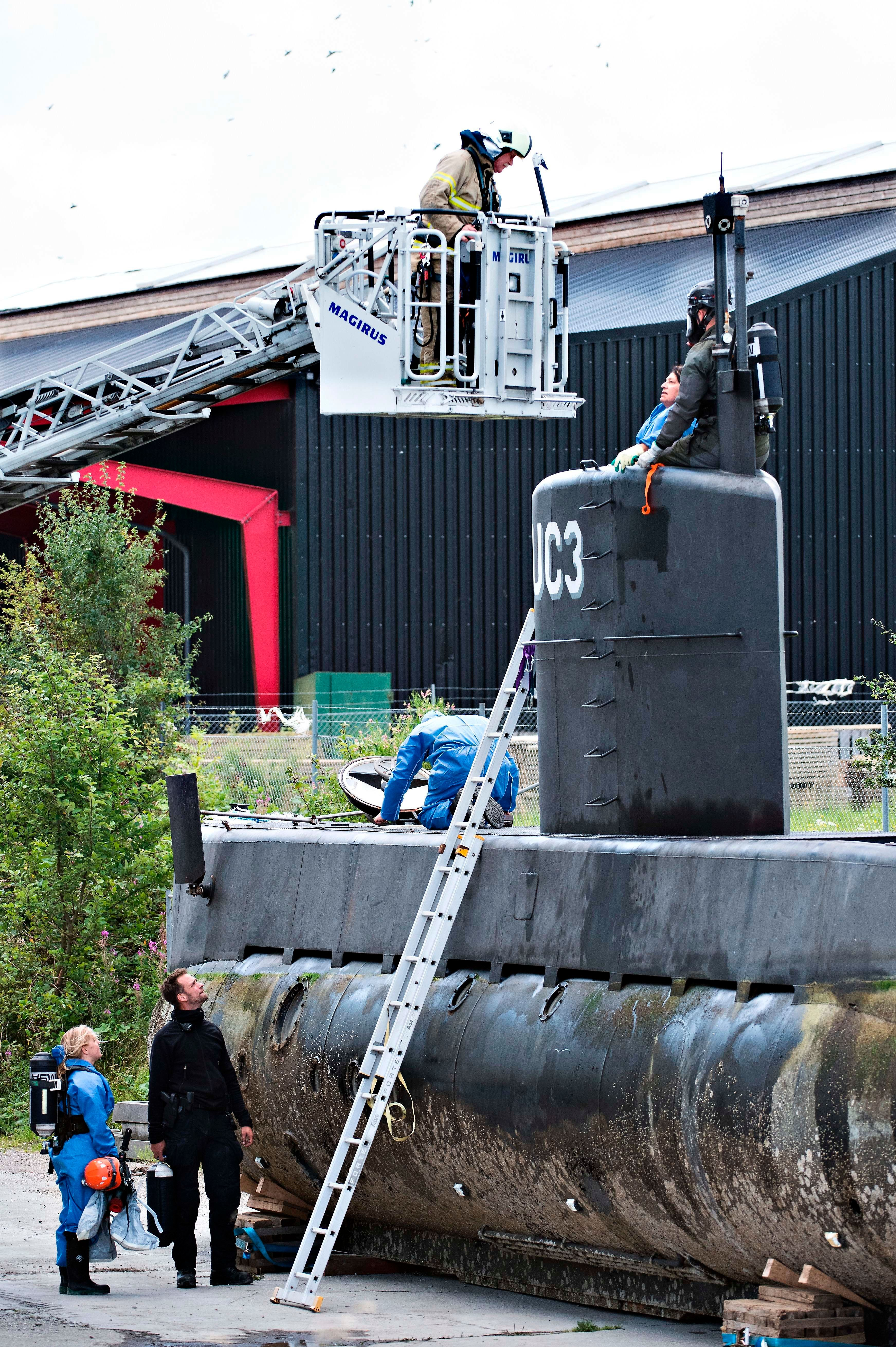 Police technicians investigate the rescued submarine on Aug. 13, 2017.