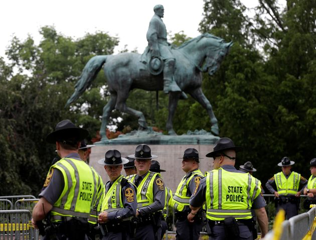 Virginia State Troopers stand under a statue of Robert E. Lee before a white supremacists rally in Charlottesville,...