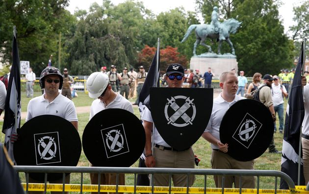 White supremacists, holding shields with a symbol of Vanguard America on them, gather under a statue...