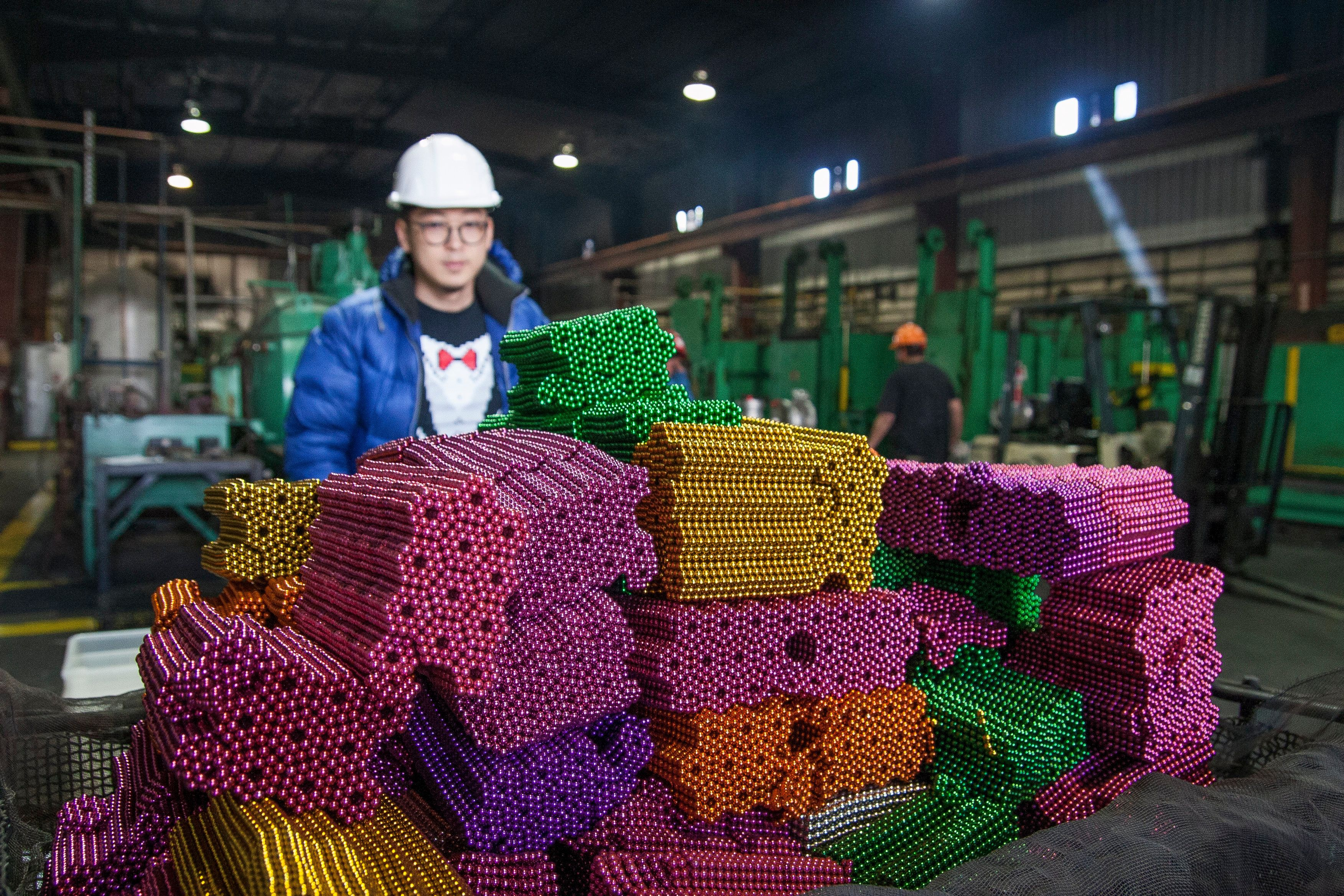 Zen Magnets founder Shihan Qu prepares high-powered magnet balls for destruction at the Metal Treating & Research Co. in