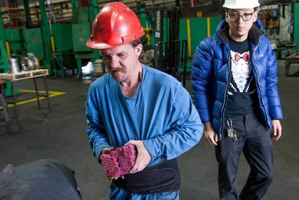 Qu looks on as a worker prepares his super-strong magnets for destruction.