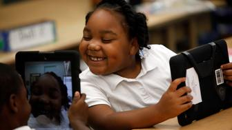 Tiannah Dizadare gives a big smile as she works with school mate  Avery Sheppard as they explore the possibilities with their new LAUSD provided IPads on AUGUST 27, 2013.  (Photo by Bob Chamberlin/Los Angeles Times via Getty Images)
