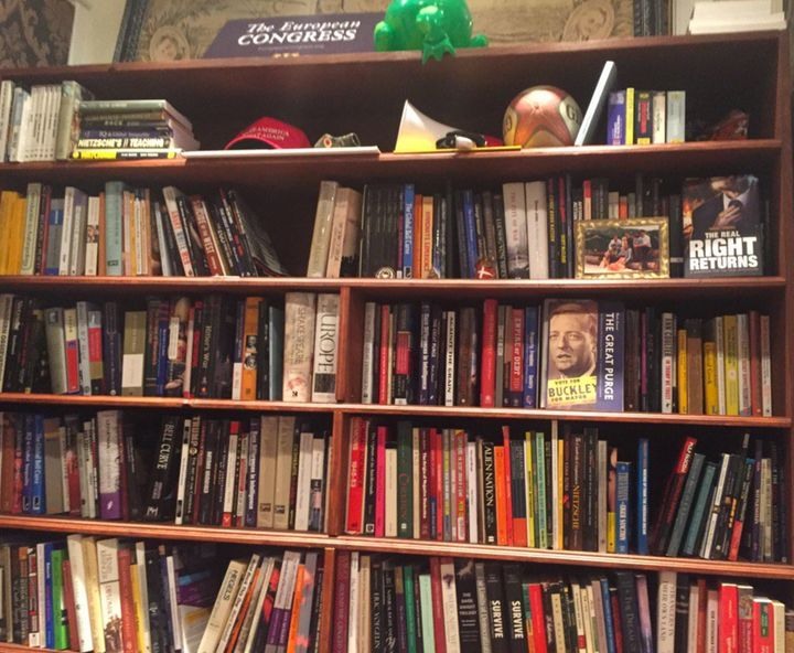 A Trump campaign hat and right-wing books fill shelves in the makeshift office in Alexandria, Virginia.