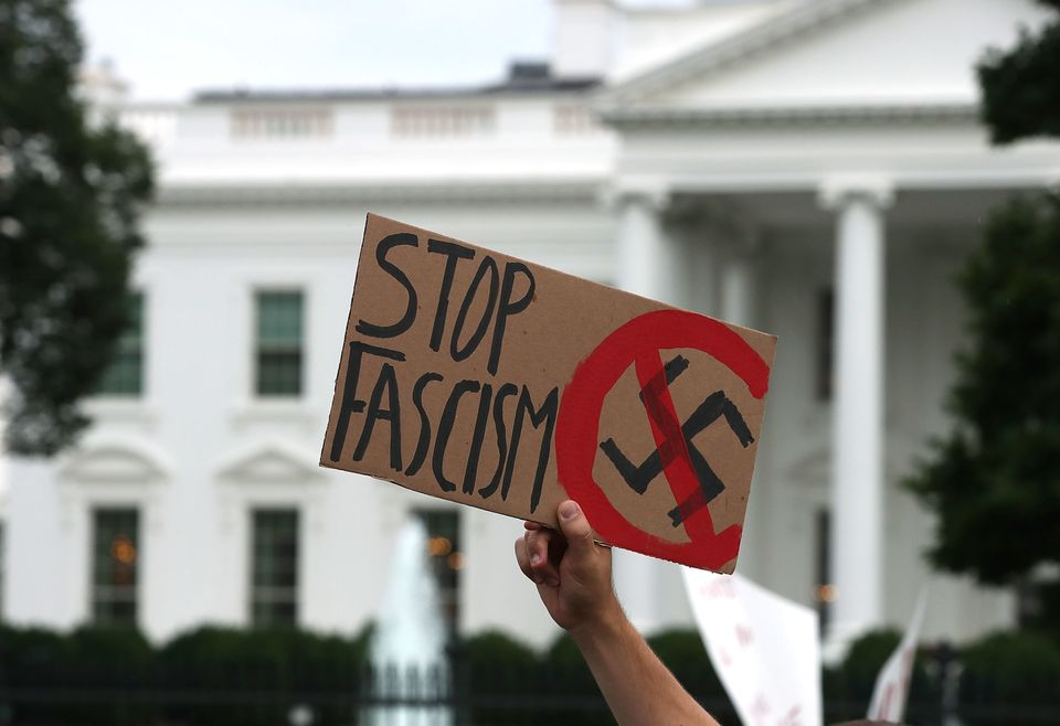A man holds up a sign during a protest against racism gathered in front of the White House, on August 14, 2017 in Washi