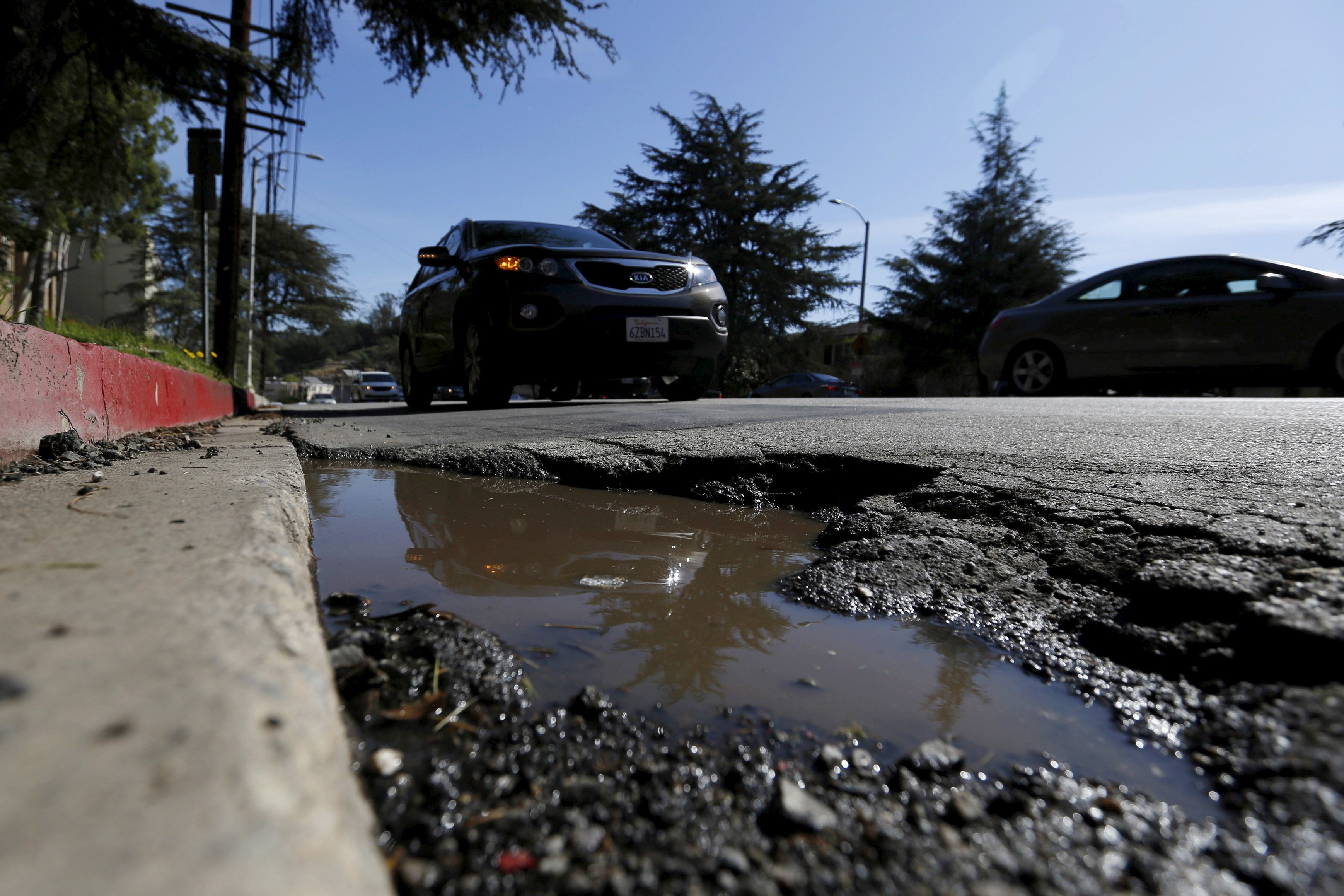 A pothole is pictured on the street of Los Angeles, California February 12, 2016. An estimated 65 percent of U.S. roads are in poor condition, according to the U.S. Department of Transportation, with the transportation infrastructure system rated 12th in the World Economic Forum's 2014-2015 global competitiveness report. Picture taken February 12. To match Insight AUTOS-AUTONOMOUS/INFRASTRUCTURE   REUTERS/Mario Anzuoni