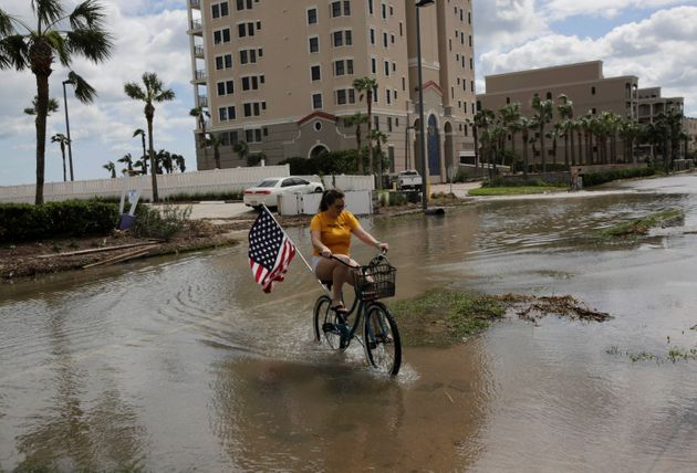 A woman rides her bicycle through a flooded street after Hurricane Matthew, near Jacksonville Beach,...
