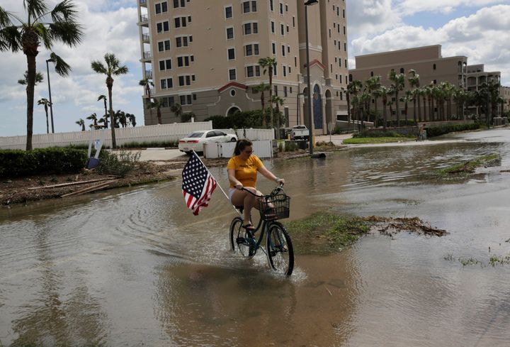 A woman rides her bicycle through a flooded street after Hurricane Matthew, near Jacksonville Beach, Florida, Oct. 8, 2016.