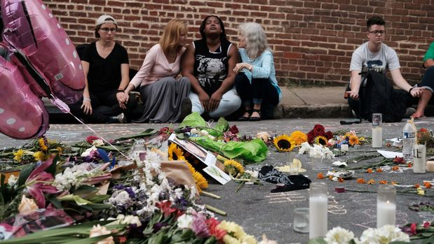 "Women sit by an impromptu memorial of flowers commemorating the victims at the scene of the car attack on a group of counter-protesters during the ""Unite the Right"" rally as people continue to react to the weekend violence in Charlottesville, Virginia, August 14, 2017. REUTERS/Justin Ide     TPX IMAGES OF THE DAY"