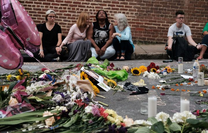 A group sits by a memorial to the victims of the deadly car attack on a group of counter-protesters during a white supremacist rally in Charlottesville, Virginia.